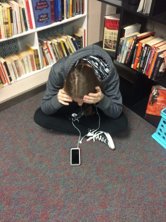 Kenzie Aldrich looks at her music library in frustration.